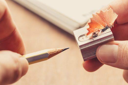Closeup hand shaving pencil to start writing