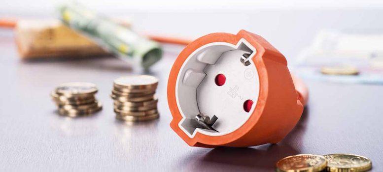 Steckdose mit Münzen und Geldscheinen
