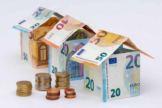Trois maisons faites en billets de 10, 20, et 50 euros, avec que